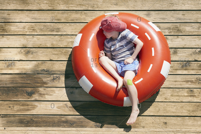 Boy sleeping in rubber ring on decking, Kraalbaai, South Africa