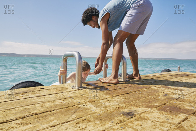 Father helping son climb on houseboat sun deck