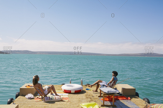 Couple relaxing on houseboat sun deck, Kraalbaai, South Africa
