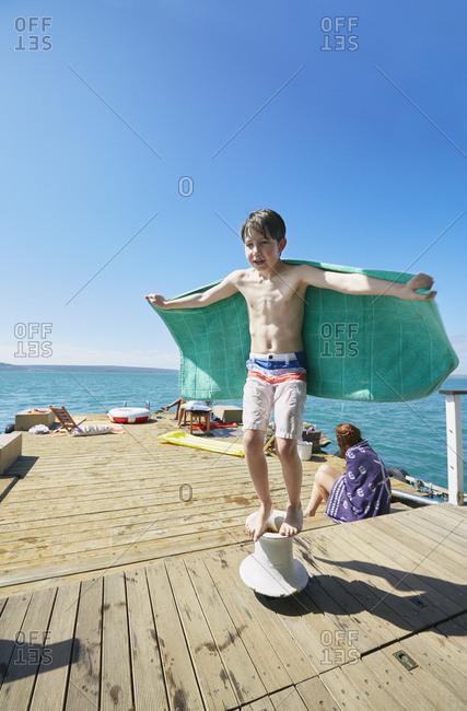 Boy balancing on mooring post on houseboat sun deck, Kraalbaai, South Africa