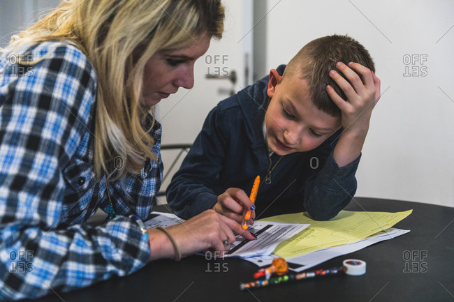 Mother and son sitting at table, mother helping son with homework