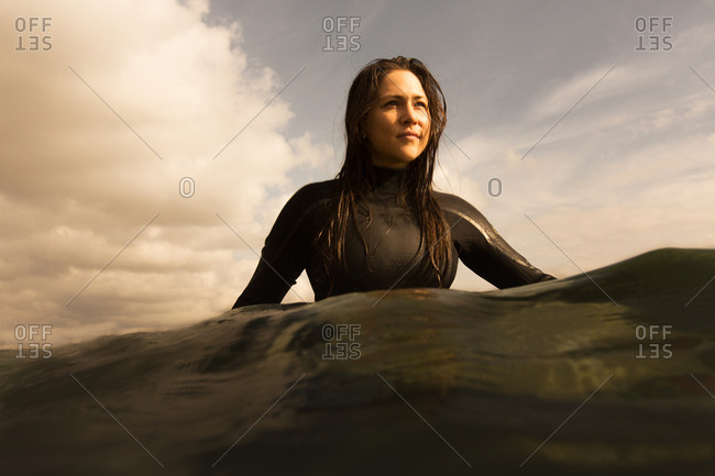 Young woman in sea, sitting on surfboard, paddling