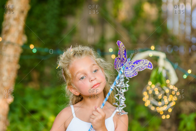 Portrait of young girl holding butterfly wand
