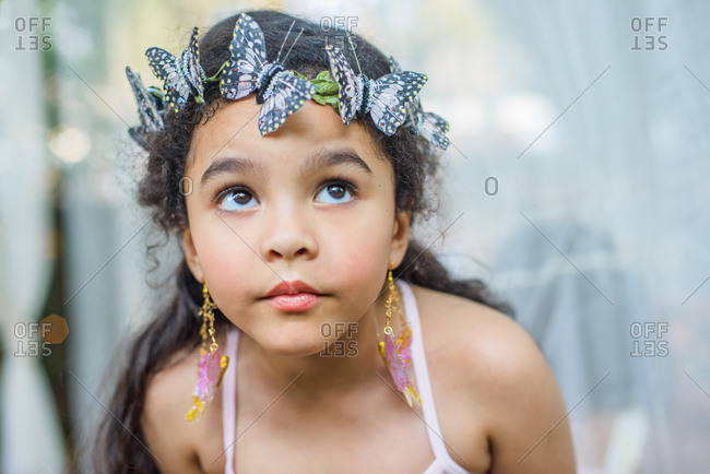 Portrait of young girl, outdoors, wearing butterflies in hair