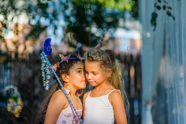 Two young girls dressed as fairies, girl whispering in friend's ear