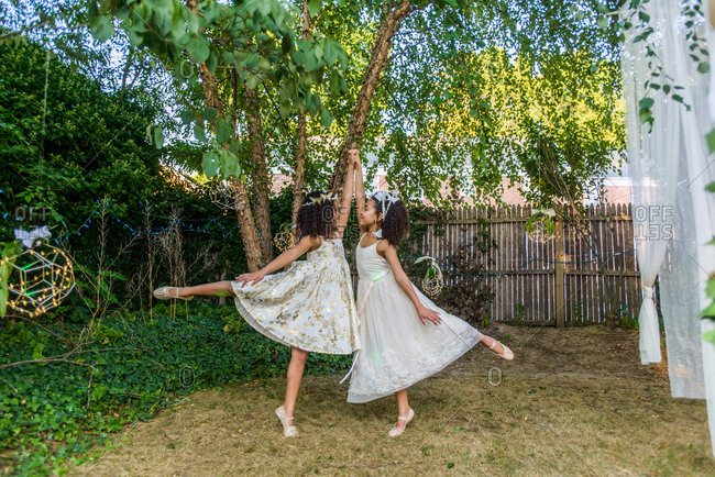 Two young girls, dressed as fairies, dancing outdoors