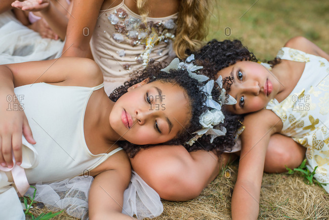 Group of young girls, dressed as fairies, lying on grass
