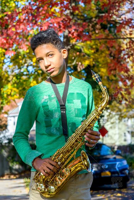 Portrait of teenage boy holding saxophone