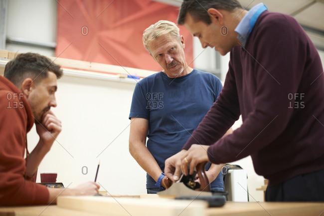 Man explaining carpentry technique in carpentry class