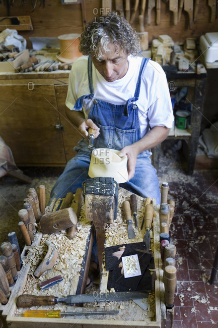 Carpenter using chisel on wooden mould for headwear in workshop