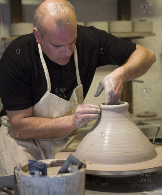Male potter shaping clay pot on pottery wheel in workshop
