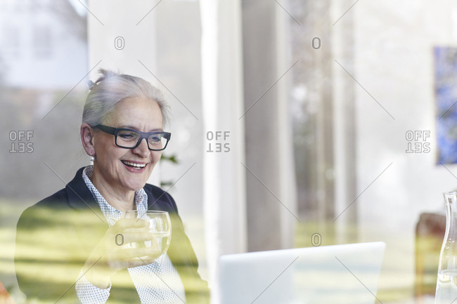 Home window view of senior businesswoman looking at laptop