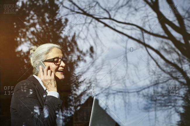 Home window view of senior businesswoman making smartphone call
