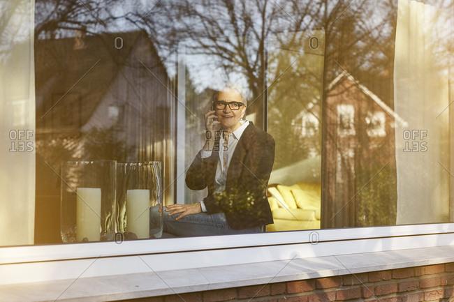 Home window view of senior businesswoman making smartphone call