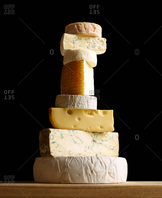 Stack of selection of cheeses, against black background