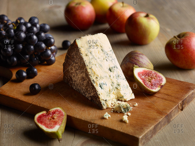 Still life of Stilton on chopping board with figs, apples and grapes