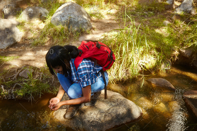 Young woman, hiking, crouching on rock beside stream, Cape Town, South Africa