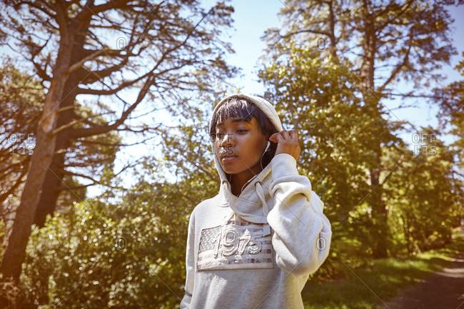 Young woman walking in rural setting, wearing hooded sweatshirt and earphones