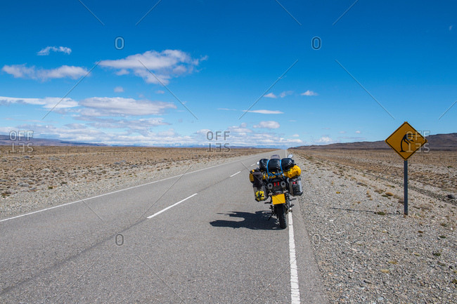 Touring motorbike parked next to road sign, warning of strong winds in Patagonia, El Chalten, Route 40, Santa Cruz province, Argentina