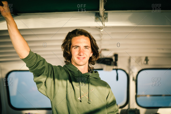 Portrait of teenage boy in fishing boat on coast of Maine, USA