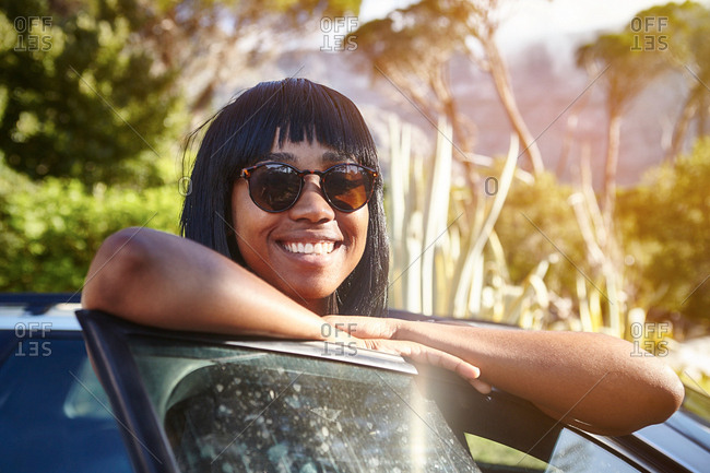 Portrait of young woman standing beside car, leaning on open car door