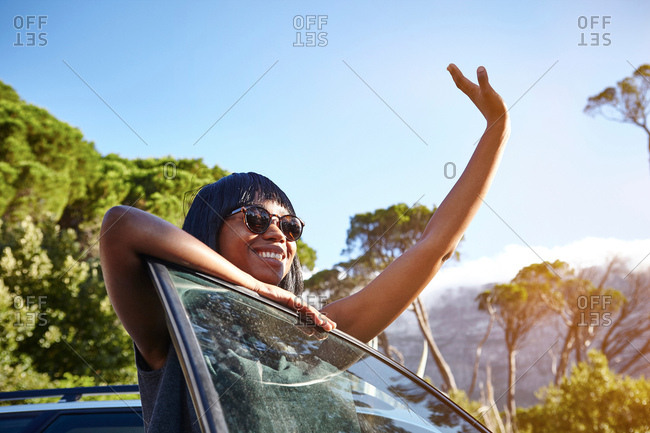 Portrait of young woman standing beside car, leaning on open car door, waving