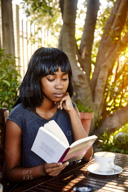 Young woman sitting outdoors, reading book, coffee in front of her