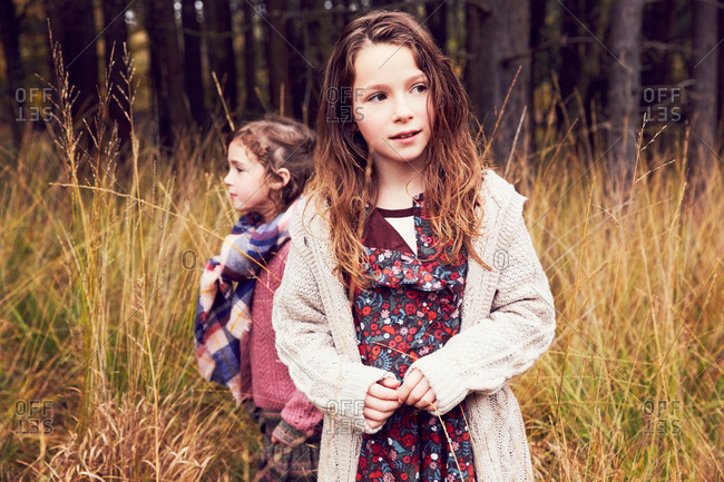 Portrait of two young standing in meadow