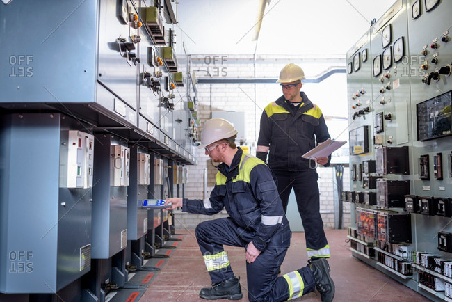 Workers testing for noise in electricity substation