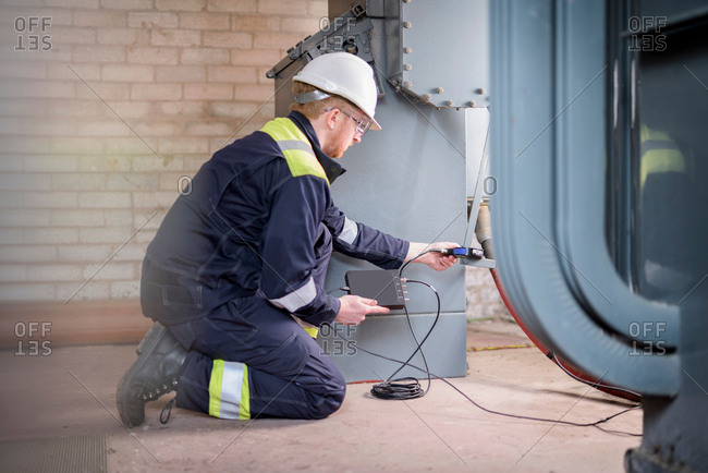 Worker testing transformers in electricity substation
