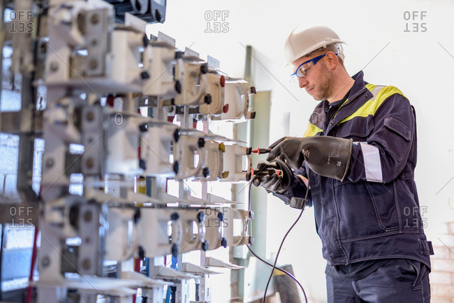 Worker testing circuit breakers in electricity substation