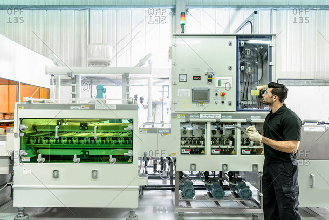 Worker with circuit board processing machine in electronics factory
