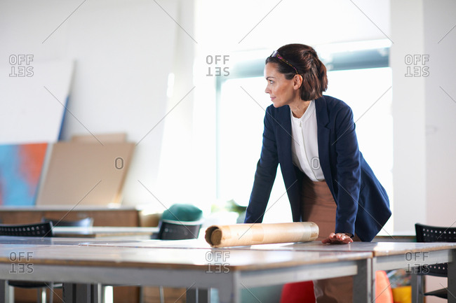 Woman in office leaning against desk looking away
