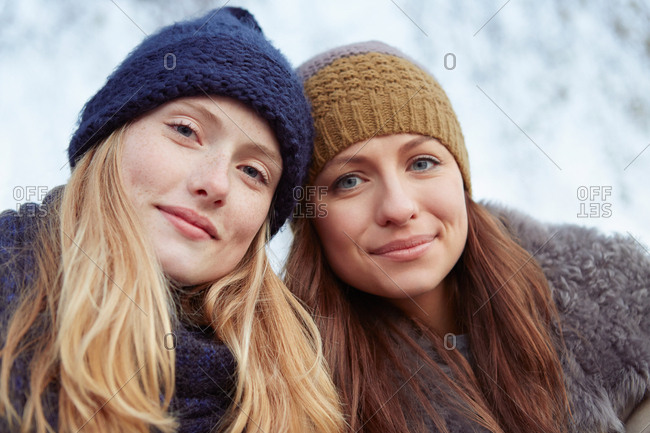 Portrait of two female friends outdoors, wearing knitted hats
