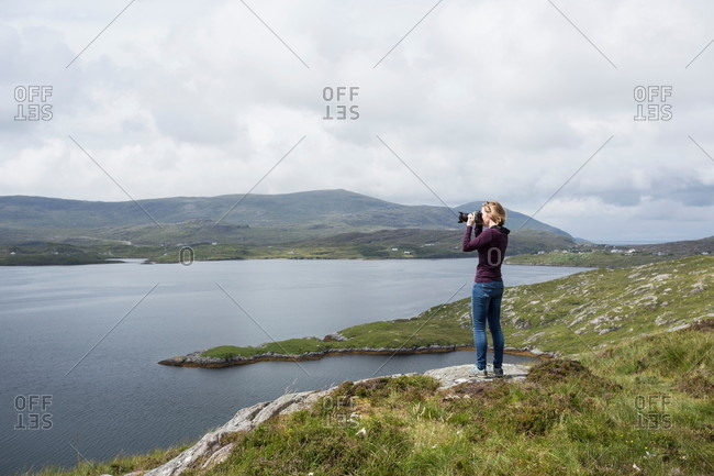 Woman photographing view, standing on north shore of East Loch Tarbet, North Harris, Outer Hebrides, Scotland