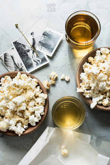 Still life of popcorn and drink, beside old black and white photographs, overhead view