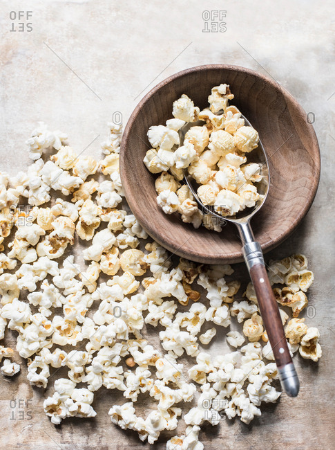 Popcorn in wooden bowl with metal scoop, overhead view
