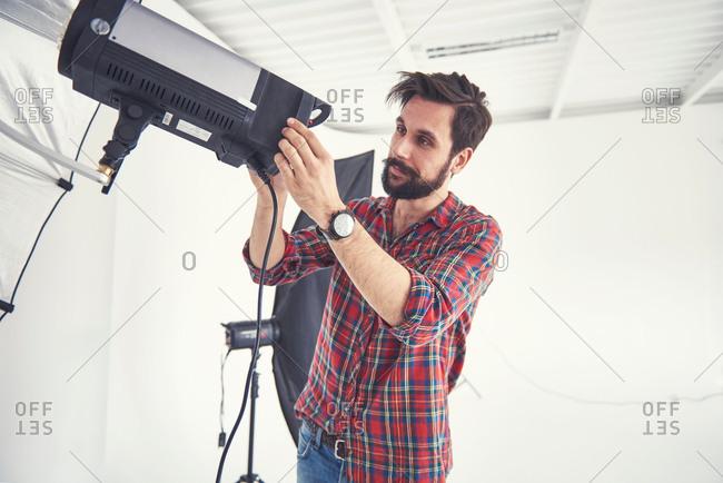 Male photographer preparing photo shoot lighting equipment   in studio