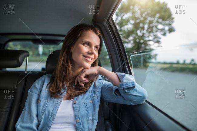 Mid adult woman looking through car window from front seat
