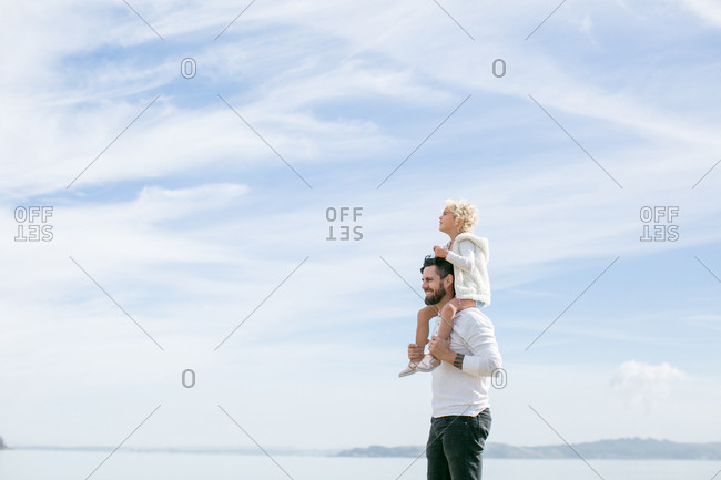 Mature man giving daughter a shoulder carry at coast
