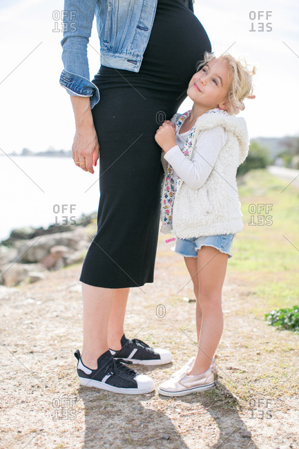 Cropped shot of pregnant mother and daughter at coast