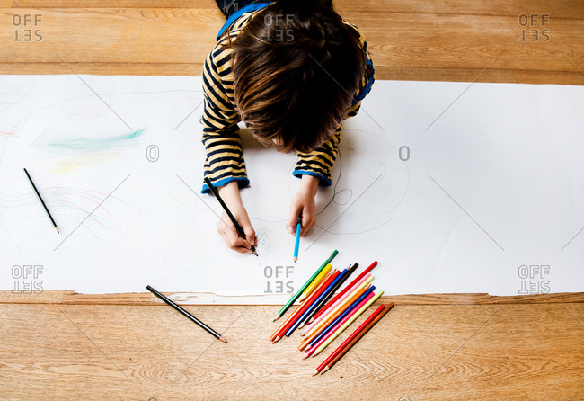 Overhead view of boy lying on floor drawing on long paper