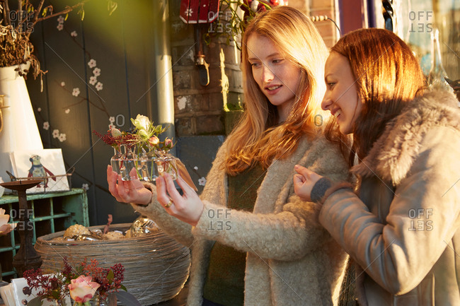 Two female friends looking at flowers, outside shop