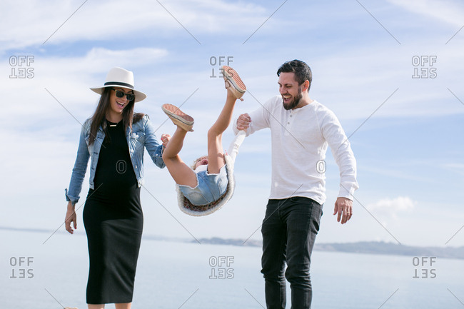 Mature couple swinging daughter at coast