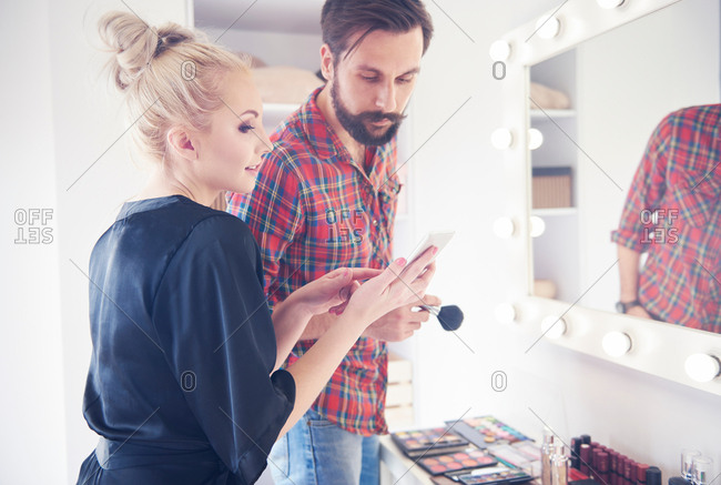 Male make up artist and model looking at smartphone before photo shoot