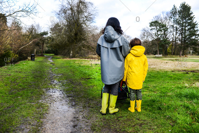 Rear view of woman with son in yellow anorak standing in park