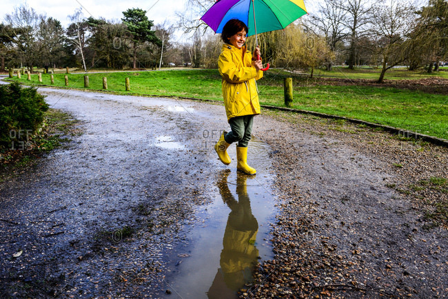 Boy in yellow anorak carrying umbrella in park