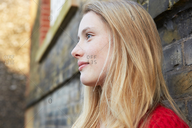 Portrait of young woman outdoors, looking away