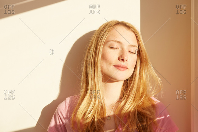 Portrait of young woman, outdoors, in sunlight, eyes closed