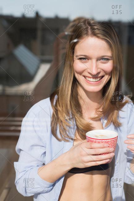 Portrait of beautiful woman wearing open shirt holding coffee  at window